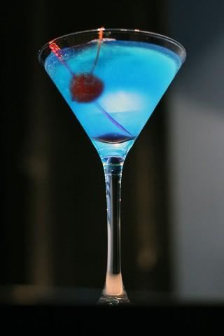 The blue cocktail garnished with red maraschini cherry (Прелестный голубой коктейль украшенный красной мараскиновой вишней)