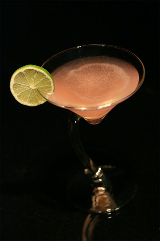 The Cosmopolitan cocktail garnished with lime wheel served in swerve glass (Коктейль Космополитан украшенный колесиком лайма в необычном коктейльном бокале)