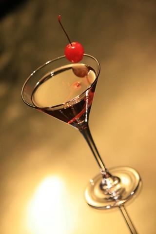 The Gin & It Cocktail garnished with a red maraschino cherry and orange peel (Коктейль Джин и Это украшенный красной мараскиновой вишенкой и полоской кожуры апельсина)