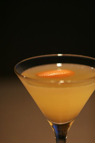 The Paradise Cocktail garnished with flammed orange peel (Коктейль Рай украшенный обожженной кожурой апельсина)