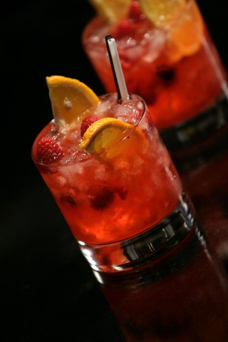 The Gin Punch garnished with orange wedges and raspberry (        )