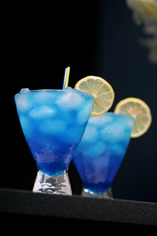 The Blue Lagoon Cocktail garnished with lemon wheel (     )