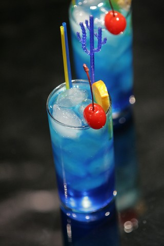 The Blue Lagoon Cocktail garnished with red maraschino cherry and orange slice (         )