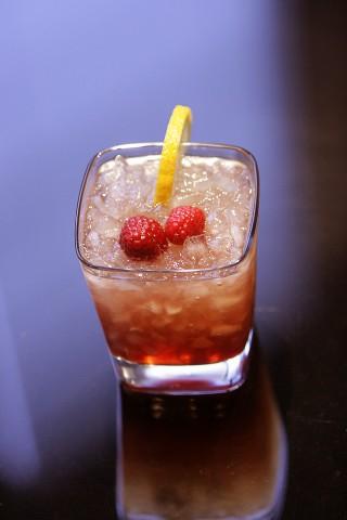 The Bramble Cocktail garnished with raspberries (Коктейль Ежевика украшенный ягодами малины)