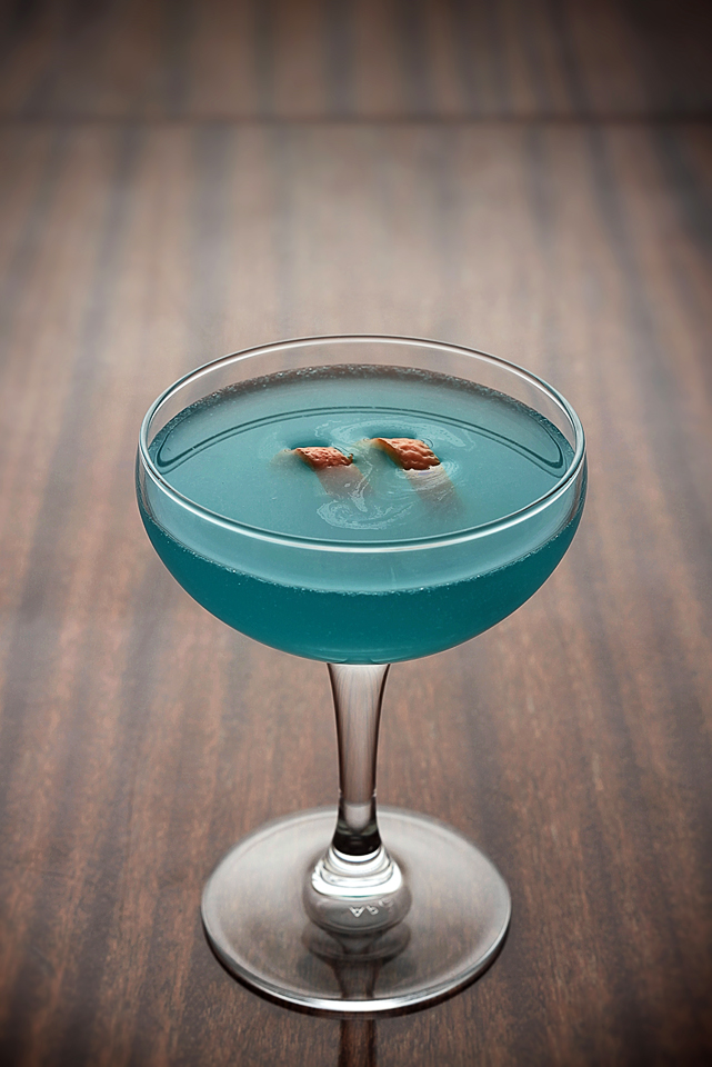 The Blue Bird Cocktail garnished with orange zest
