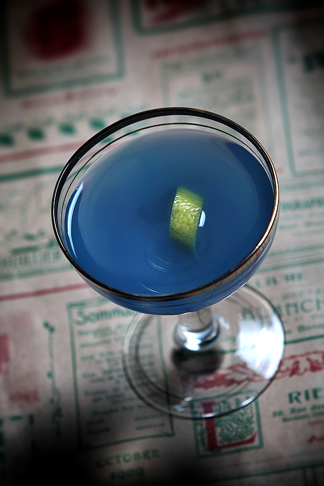 The Blue Cocktail garnished with a lemon twist in a vintage glass