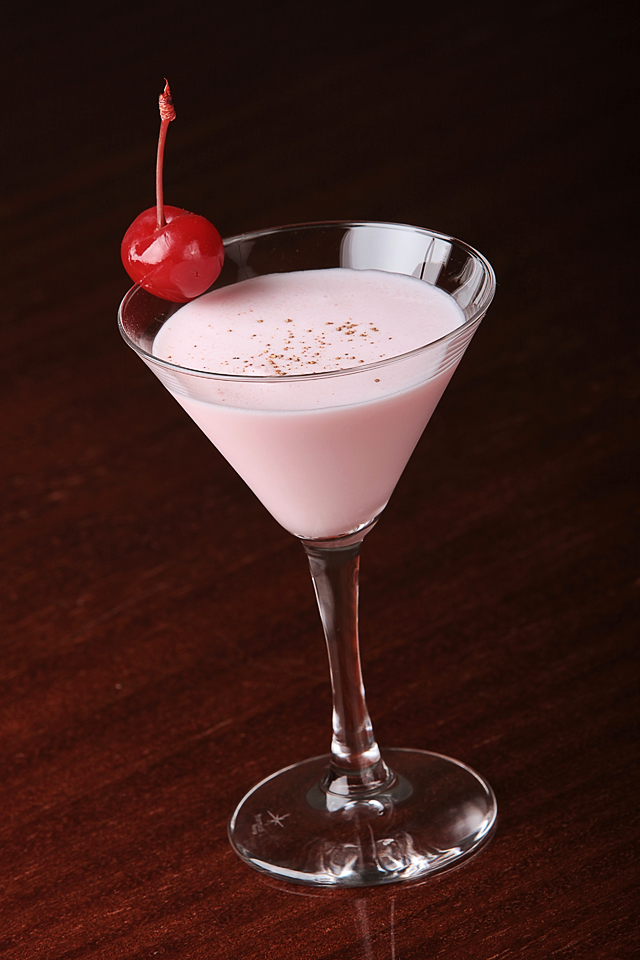 Beauty pink Silk Stockings Cocktail garnished with a red maraschino cherry