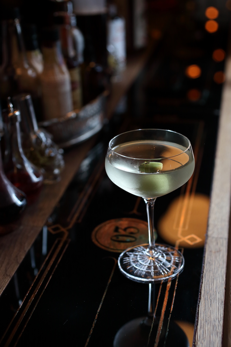 The Dry Martini Cocktail with a green olive | ScienceOfDrink.com
